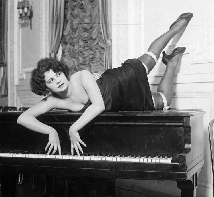 Woman atop a piano in a state of déshabillé, 1920s
