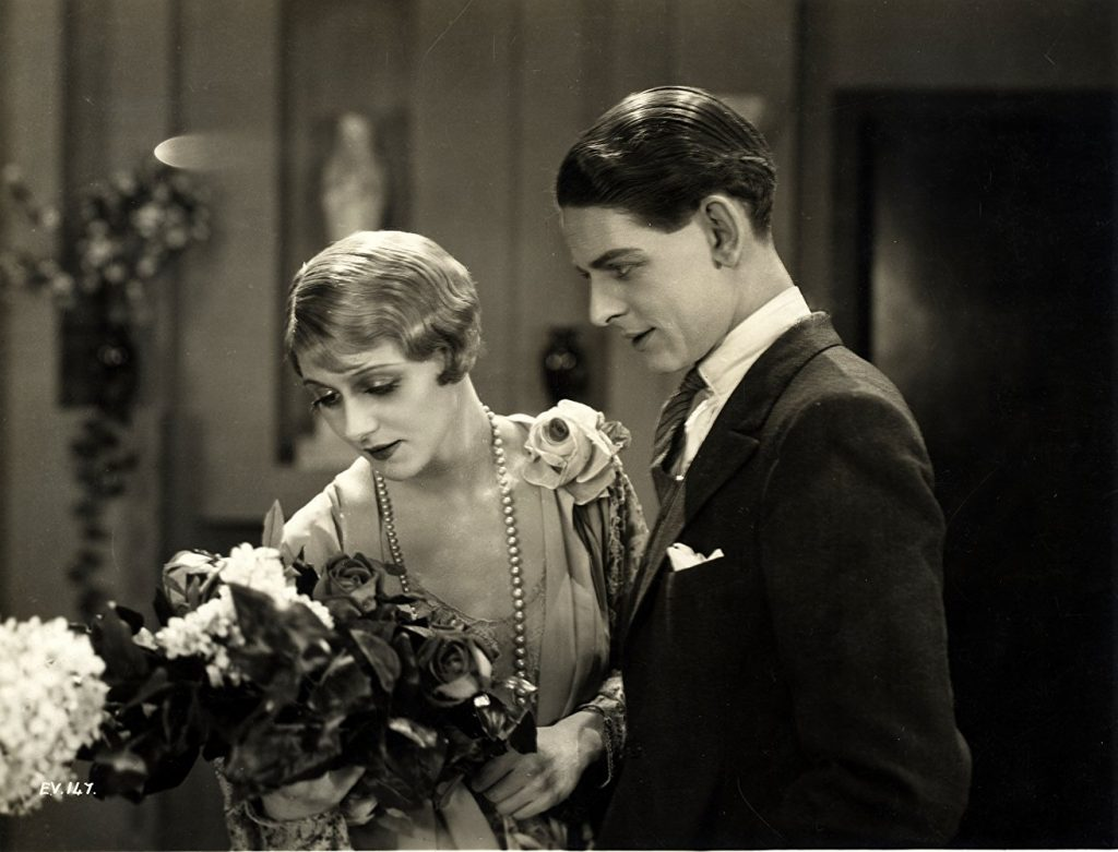 A glamorously-dressed Isabel Jeans and Robin Irvine in Easy Virtue (1927, dir. Alfred Hitchcock). She admires a bunch of flowers while he admires her, with lust.